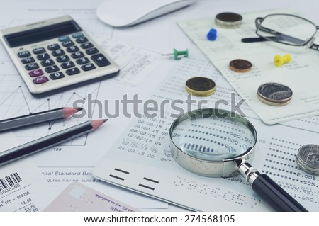Magnifying glass, pencil, account book, glasses, coin on paper chart, saving concept - stock photo