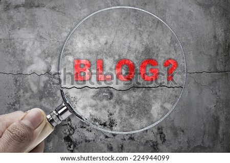 """Magnifying glass searching """"blog"""" over cracked wall as a background - stock photo"""