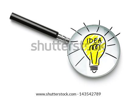 Magnifying glass searching for a good idea light bulb isolated on white - stock photo