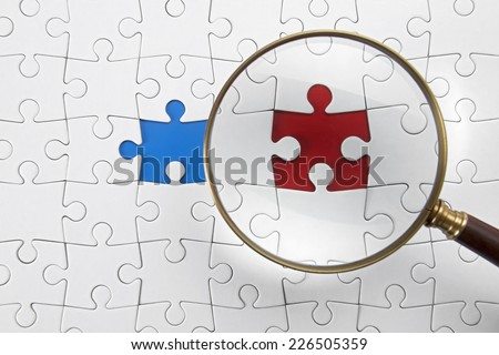 Magnifying glass searching missing puzzle peace  - stock photo
