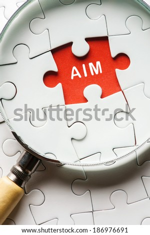 "Magnifying glass searching missing puzzle peace ""AIM"" - stock photo"