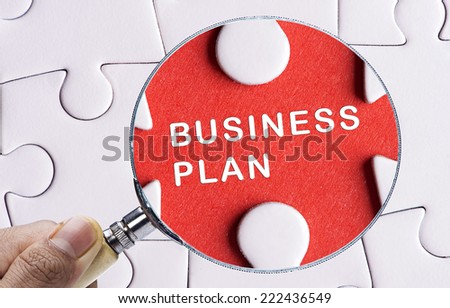 """Magnifying glass searching missing puzzle peace """"BUSINESS PLAN"""" - stock photo"""