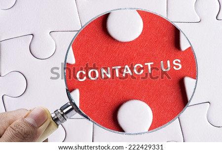 """Magnifying glass searching missing puzzle peace """"CONTACT US"""" - stock photo"""