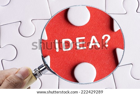 "Magnifying glass searching missing puzzle peace ""IDEA"" - stock photo"