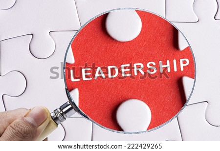 "Magnifying glass searching missing puzzle peace ""LEADERSHIP"" - stock photo"