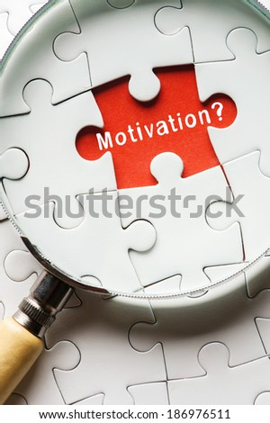 "Magnifying glass searching missing puzzle peace ""MOTIVATION"" - stock photo"