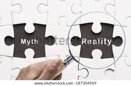 "Magnifying glass searching missing puzzle peace ""Reality"" - stock photo"