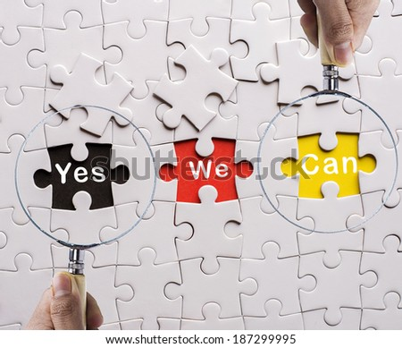 "Magnifying glass searching missing puzzle peace ""Yes&Can"" - stock photo"