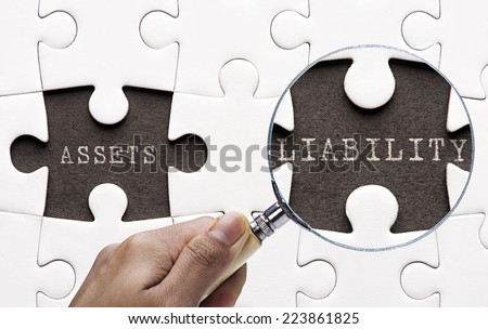 "Magnifying glass searching missing puzzle peaces ""Asset and Liability""  - stock photo"