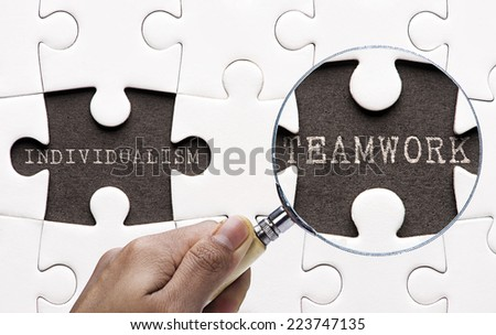 "Magnifying glass searching missing puzzle peaces ""Individualism and Teamwork""  - stock photo"