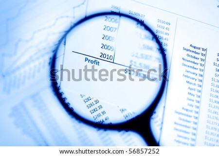 Magnifying glass showing profits - stock photo