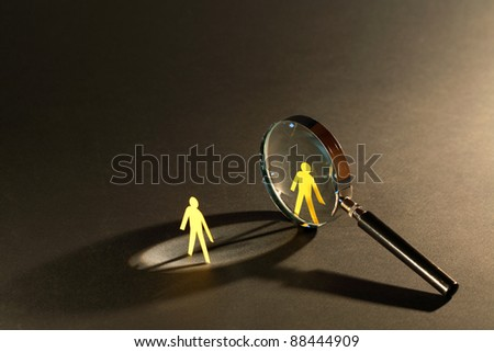Magnifying glass standing between two small paper men on dark surface - stock photo