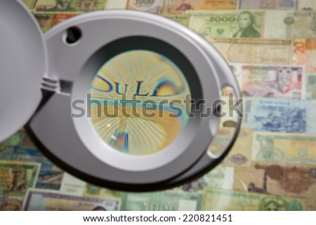 Magnifying glass through which can be seen banknote banknotes of different countries - stock photo