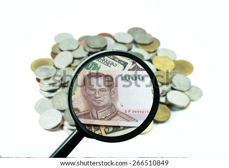 magnifying glass with background of coins to be dollar, business concept - stock photo