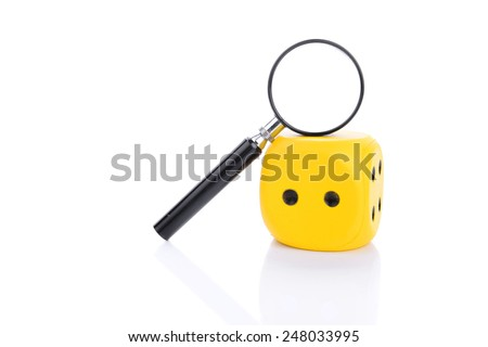 Magnifying glass with dice isolated on white background - stock photo