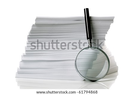 Magnifying glass with stack of documents - concept for searching for a file - stock photo