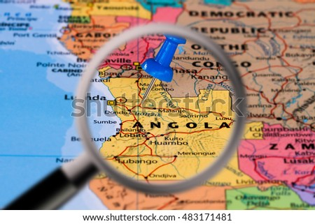 Magnifying glass with the Map of Angola with a blue pushpin stuck