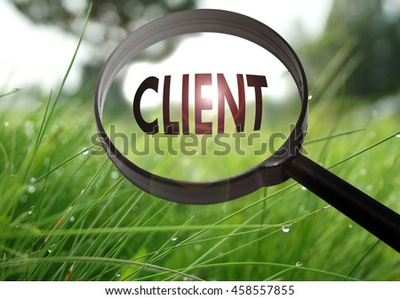 Magnifying glass with the word client on grass background. Selective focus - stock photo