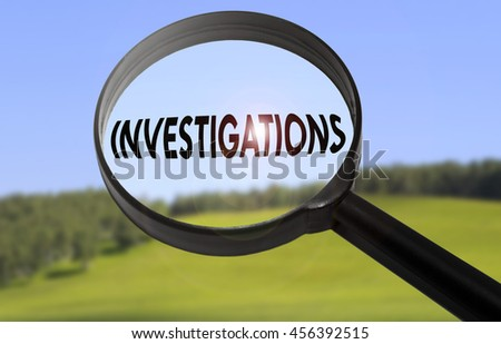 Magnifying glass with the word investigations on blurred nature background - stock photo