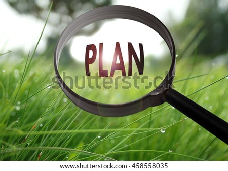 Magnifying glass with the word plan on grass background. Selective focus - stock photo