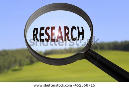 Magnifying glass with the word research on blurred nature background - stock photo