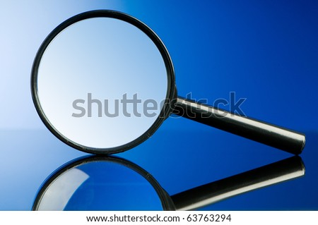 Magnifying glass with wooden handle on the flat surface - stock photo