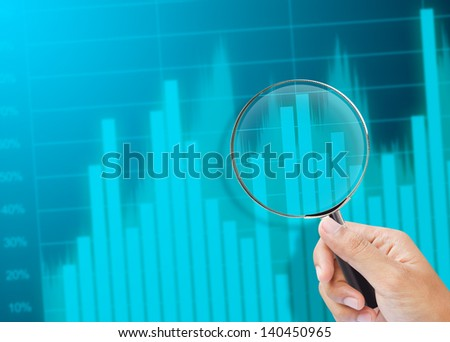 magnifying glass zoom on a business chart - stock photo