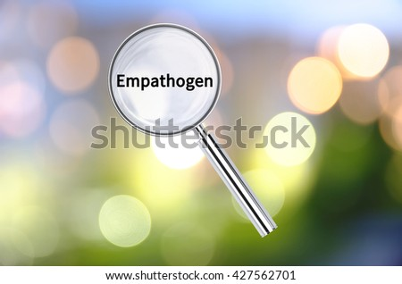 Magnifying lens over background with text Empathogen, with the blurred lights visible in the background. 3D rendering. - stock photo