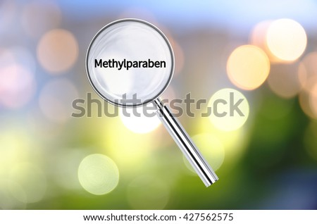 Magnifying lens over background with text Methylparaben, with the blurred lights visible in the background. 3D rendering. - stock photo