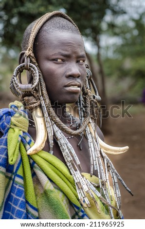 MAGO NATIONAL PARK, ETHIOPIA - August 10: unidentified woman from Mursi Tribe on August 10 2014. Mursi wear many ornaments made by natural materials, like elephant teeth. - stock photo