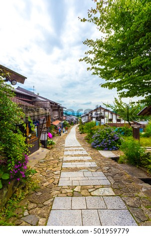 Magome, Japan - June 30, 2015: Tourists visit a restaurant housed in restored wooden buildings on a traditional stone path on the ancient Magome-Tsumago portion of Nakasendo trail. Vertical