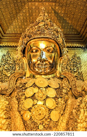 Mahamuni golden Buddha statue at Mahamuni Buddha temple in Mandalay, Myanmar. It is the most ancient Buddha image in Myanmar.  - stock photo