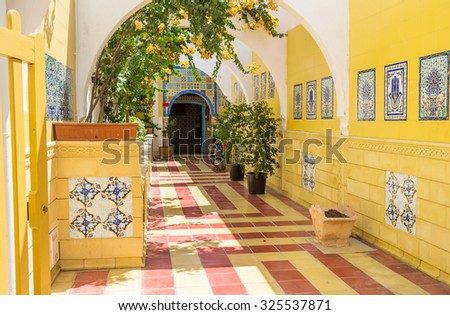 MAHDIA, TUNISIA - AUGUST 29, 2015: The entrance to the public bath decorated with the traditional arabic tiles and flowers in pots, on August 29 in Mahdia.