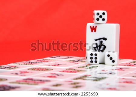 Mahjong wind tile and dice sitting on top of mahjong playing - stock photo