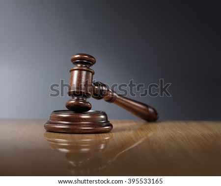 Mahogany wooden gavel on glossy wooden table. - stock photo