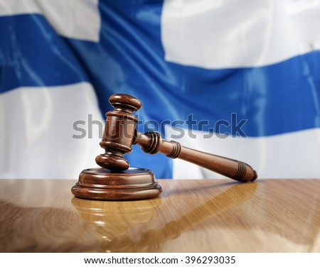 Mahogany wooden gavel on glossy wooden table, flag of Finland in the background.