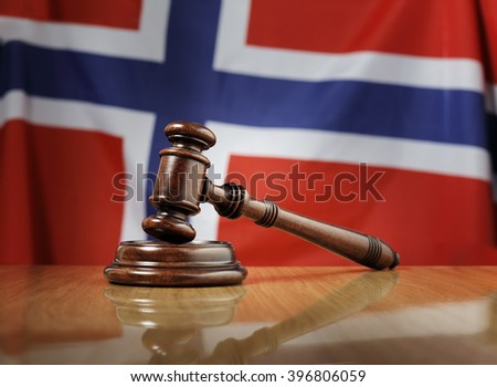 Mahogany wooden gavel on glossy wooden table, flag of Norway in the background. - stock photo
