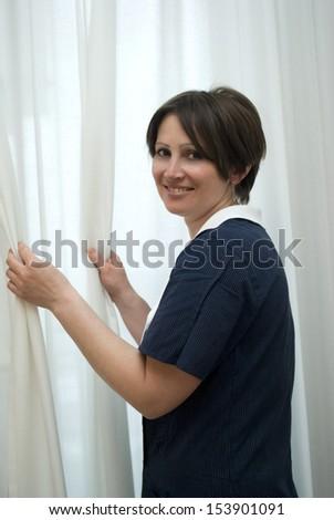 Maid drawing curtain - stock photo