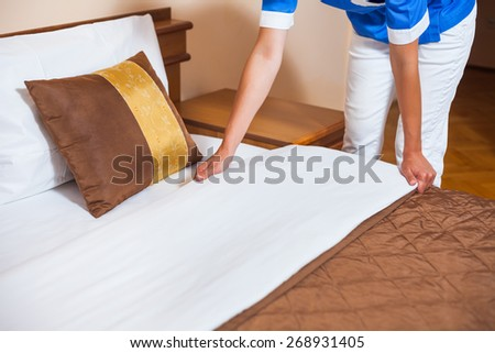 Maid making bed in hotel room - stock photo