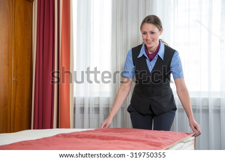 Maid or room service making the bed in a hotel room - stock photo