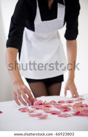 Maid preparing heart with petals on honeymooners' bed - stock photo