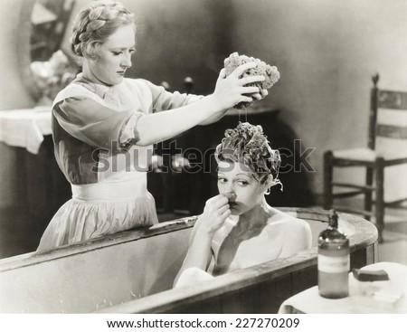 Maid squeezing sponge on woman in bathtub - stock photo
