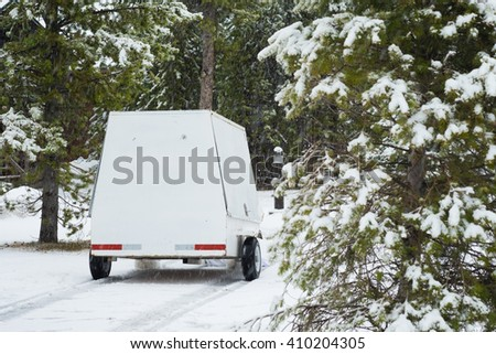 Maid trolley in walkway surrounded by trees, spruce, covered in snow - stock photo