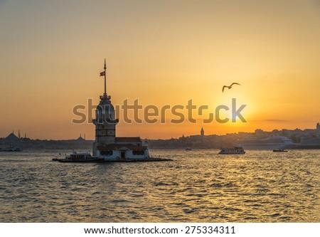 Maiden's Tower (Kiz Kulesi) at sunset with flying seagull. Istanbul, Turkey - stock photo