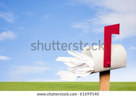 Mail box overflowing with mail against sky - stock photo