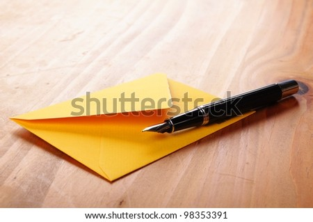 mail or email concept with envelope and pen - stock photo