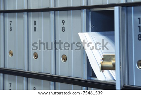 mail waiting in the u.s. grey/blue post office box - stock photo