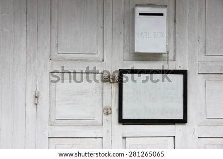 Mailbox and sign board blank frame on old wood door - stock photo
