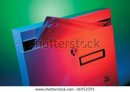 Mailbox full of letters on very colorful background - stock photo
