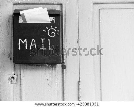 Mailbox on wooden door. Black and white. - stock photo